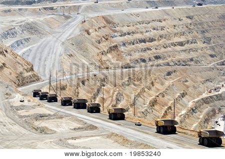 A long line of monster dump trucks drives down into an open pit mine to pick up their next load