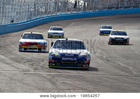 AVONDALE, AZ - APRIL 10: Jimmie Johnson (#58) leads a group of cars out of turn two at the Subway Fresh Fit 600 NASCAR Sprint Cup race on April 10, 2010 in Avondale, AZ.