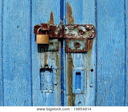 Cerradura oxidada y dependen de viejas puertas de azules.