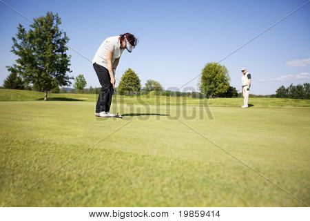 Couple of active senior golf players competing, woman concentrating for putting on green on beautiful golf course with blue sky in background.