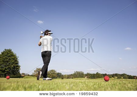 Active senior female golf player swinging golf club to tee off ball on beautiful golf course with blue sky in background.