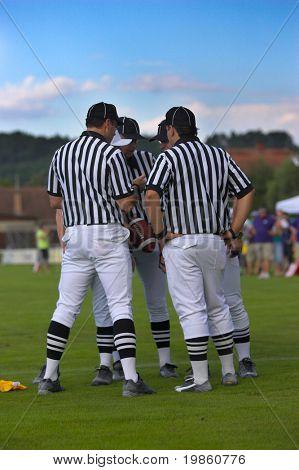 Equipo de árbitros de fútbol discutir su decisión. Un marcador de pena puede verse en el suelo.