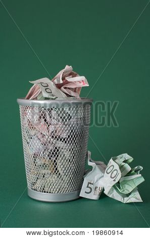 Photo of a waste basket full of money.