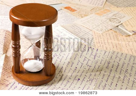 Hourglass on old letters as a background