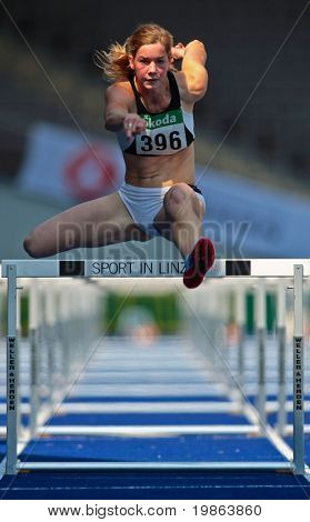 LINZ, AUSTRIA - AUGUST 2 Austrian track and field championship: Beate Schrott (#396) wins the women's 100m hurdles event on August 2, 2009 in Linz, Austria.