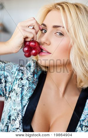 closeup portrait of attractive blond woman holding grape