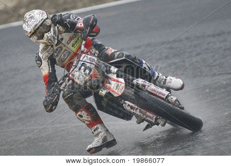 MILAN ITALY JUNE 24 Christian Iddon GB rips of a visor cover while competing in the FIM Supermoto World Championship CASTELLETTO DI BRANDUZZO ITALY