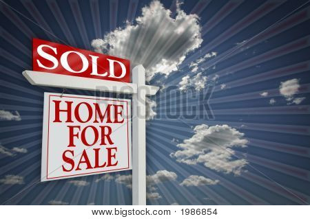 Sold Home For Sale Sign On Burst & Sky With Clouds