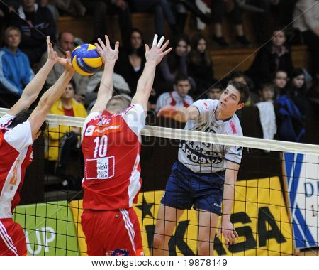 KAPOSVAR, HUNGARY - DECEMBER 8: Istvan Schulcz (in white) strikes the ball at a CEV Cup volleyball game Kaposvar (HUN) vs Hotvolleys Wien (AUT), December 8, 2009 in Kaposvar, Hungary