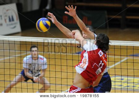 KAPOSVAR, HUNGARY - DECEMBER 8: Peter Nagy (in red) strikes the ball at a CEV Cup volleyball game Kaposvar (HUN) vs Hotvolleys Wien (AUT), December 8, 2009 in Kaposvar, Hungary