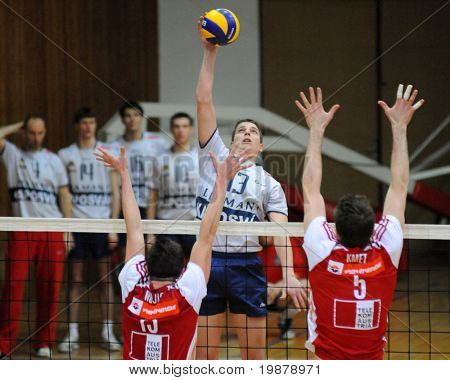 KAPOSVAR, HUNGARY - JANUARY 22: Istvan Schulcz (C) strikes the ball at a Middle European League volleyball game Kaposvar (HUN) vs. HotVolleys Wien (AUT), January 22, 2010 in Kaposvar, Hungary.