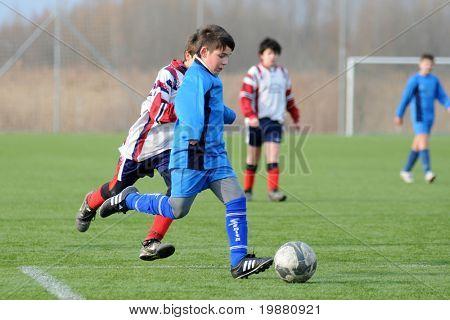 KAPOSVAR, HUNGARY - MARCH 6: Soma Ozorai (in blue) in action at the Hungarian National Championship under 13 game between Kaposvari Rakoczi FC and Mezga FC March 6, 2010 in Kaposvar, Hungary.