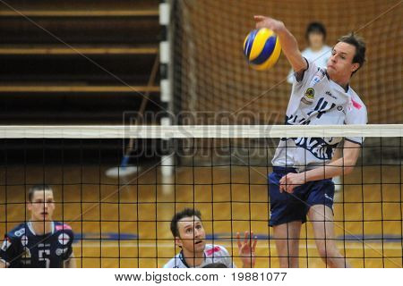 KAPOSVAR, HUNGARY - MARCH 7: Krisztian Csoma (R) strikes the ball at a Middle European League volleyball game Kaposvar (HUN) vs. Salonit Anhovo (SLO), March 7, 2010 in Kaposvar, Hungary.