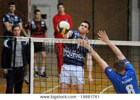 KAPOSVAR, HUNGARY - MARCH 22: Akos Hoboth (C) strikes the ball at a Hungarian National Championship volleyball game Kaposvar vs. Veszprem, March 22, 2010 in Kaposvar, Hungary.