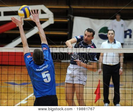 KAPOSVAR, HUNGARY - MARCH 22: Sandor Kantor (C) strikes the ball at a Hungarian National Championship volleyball game Kaposvar vs. Veszprem, March 22, 2010 in Kaposvar, Hungary.