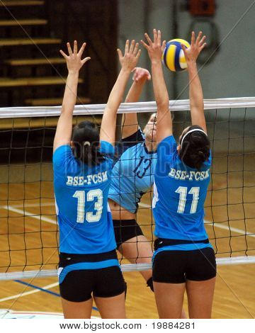 KAPOSVAR, HUNGARY - FEBRUARY 20: Gabriella Kondor (C) strikes the ball at the Hungarian Cup woman volleyball game Kaposvar vs. BSE, February 20, 2008 in Kaposvar, Hungary.