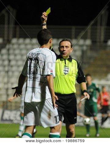 KAPOSVAR, HUNGARY - AUGUST 14: Zsolt Szabo (FIFA referre) presents a yellow card at a Hungarian National Championship soccer game Kaposvar vs. Haladas August 14, 2010 in Kaposvar, Hungary.