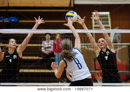 KAPOSVAR, HUNGARY - JANUARY 28: Timea Kondor (C) strikes the ball at the Hungarian Extra League woman volleyball game Kaposvar vs Godollo, January 28, 2007 in Kaposvar, Hungary.