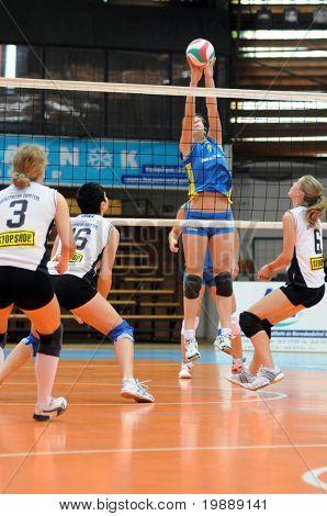 KAPOSVAR, HUNGARY - OCTOBER 10: Rebeka Rak (2nd R) blocks the ball at the Hungarian NB I. League woman volleyball game Kaposvar vs Veszprem, October 10, 2010 in Kaposvar, Hungary.
