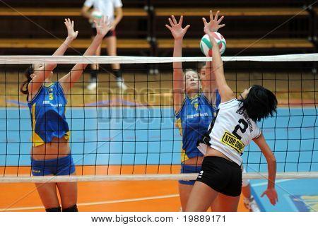 KAPOSVAR, HUNGARY - OCTOBER 10: Dora Szelle (R) strikes the ball at the Hungarian NB I. League woman volleyball game Kaposvar vs Veszprem, October 10, 2010 in Kaposvar, Hungary.