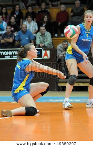 KAPOSVAR, HUNGARY - OCTOBER 10: Zsanett Pinter (L) receives the ball at the Hungarian NB I. League woman volleyball game Kaposvar vs Veszprem, October 10, 2010 in Kaposvar, Hungary.