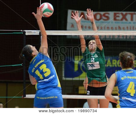 KAPOSVAR, HUNGARY - NOVEMBER 14: Gabriella Kondor (L) strikes the ball at the Hungarian NB I. League woman volleyball game Kaposvar vs Miskolc on November 14, 2010 in Kaposvar, Hungary.