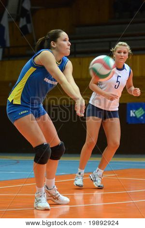 KAPOSVAR, HUNGARY - DECEMBER 19: Szandra Szombathelyi (L) receives the ball at the Hungarian NB I. League woman volleyball game Kaposvar vs Palota Bollhoff on December 19, 2010 in Kaposvar, Hungary.