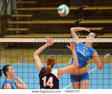 KAPOSVAR, HUNGARY - JANUARY 14: Zsofia Harmath (R) strikes the ball at the Hungarian NB I. League woman volleyball game Kaposvar vs Ujbuda, January 14, 2011 in Kaposvar, Hungary.