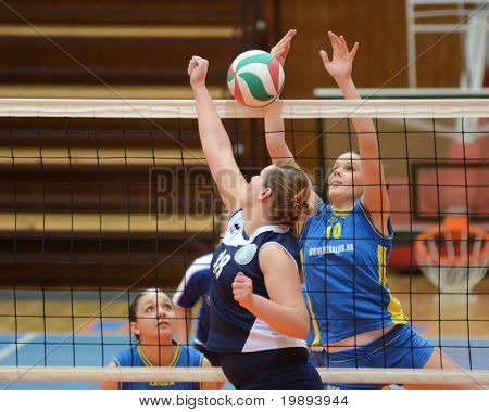 KAPOSVAR, HUNGARY - JANUARY 14: Szandra Szombathelyi (R) blocks the ball at the Hungarian NB I. League woman volleyball game Kaposvar vs Ujbuda, January 14, 2011 in Kaposvar, Hungary.