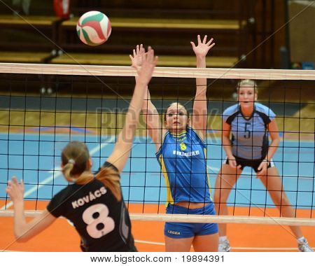 KAPOSVAR, HUNGARY - JANUARY 23: Barbara Balajcza (C) blocks the ball at the Hungarian NB I. League woman volleyball game Kaposvar vs Miskolc, January 23, 2011 in Kaposvar, Hungary.