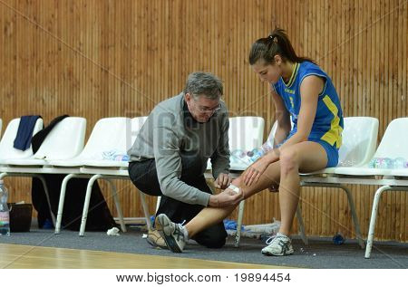KAPOSVAR, HUNGARY - JANUARY 23: The doctor heals it the Zsofia Harmath wound at the Hungarian NB I. League woman volleyball game Kaposvar vs Miskolc, January 23, 2011 in Kaposvar, Hungary.