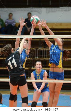 KAPOSVAR, HUNGARY - JANUARY 23: Zsofia Harmath (R) blocks the ball at the Hungarian NB I. League woman volleyball game Kaposvar vs Miskolc, January 23, 2011 in Kaposvar, Hungary.