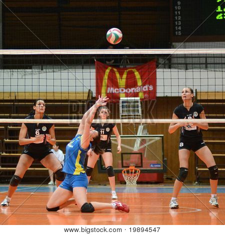 KAPOSVAR, HUNGARY - JANUARY 23: Marianna Palfy (in blue) posts the ball at the Hungarian NB I. League woman volleyball game Kaposvar vs Miskolc, January 23, 2011 in Kaposvar, Hungary.