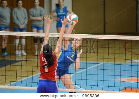 KAPOSVAR, HUNGARY - FEBRUARY 4: Zsanett Pinter (R) strikes the ball at the Hungarian NB I. League woman volleyball game Kaposvar vs Szolnok, February 4, 2011 in Kaposvar, Hungary.
