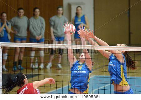 KAPOSVAR, HUNGARY - FEBRUARY 4: Barbara Balajcza (C) blocks the ball at the Hungarian NB I. League woman volleyball game Kaposvar vs Szolnok, February 4, 2011 in Kaposvar, Hungary.