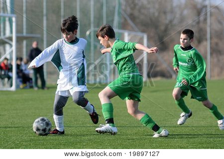 KAPOSVAR, HUNGARY - MARCH 9: Mark Krall (C) and Soma Ozorai (L) in action at the Hungarian National Championship under 13 game between Kaposvar and Airnergy FC on March 9, 2011 in Kaposvar, Hungary.