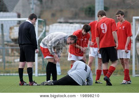 KAPOSVAR, HUNGARY - MARCH 13:Tamas Toth (1) complains of a pain in his foot at the Hungarian National Championship under 17 game between Kaposvar and Mohacs on March 13, 2011 in Kaposvar, Hungary.