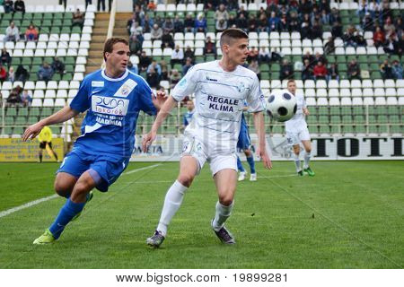 KAPOSVAR, HUNGARY - APRIL 16: Benjamin Balazs (in white) in action at a Hungarian National Championship soccer game - Kaposvar vs MTK Budapest on April 16, 2011 in Kaposvar, Hungary.
