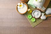 Beautiful spa composition with coconut body care products on bamboo mat poster