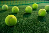 Close up of tennis balls on court by net poster