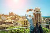 Woman tourist with her phone camera in hands shooting in Palma de Mallorca under sunlight and blue s poster