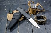 A Military Knife, A Survival Bracelet And A Metal Glass In The Skin. poster