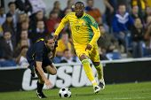LONDON, UK AUGUST 19, Benni Macarthy out runs Mark Milligan playing in the international football fr