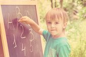 Cute Little Boy At Blackboard Practicing Counting And Math Outdoor. Toned. poster