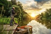 Sport fisherman hunting predator fish from wooden pier. Outdoor fishing in river during sunrise. Hun poster