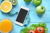 Mobile phone and healthy food on wooden table. Weight loss concept poster