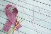 Close-up of pink Breast Cancer Awareness ribbon by crochet needles with heart shape on white wooden  poster
