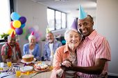 Portrait of senior couple standing by table during birthday party with friends in background poster