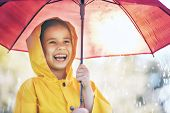 Happy funny child with red umbrella under the autumn shower. Girl is wearing yellow raincoat and enj poster