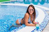 Seductive Girl In Blue Dress Relaxing At Swimming Pool Edge Poolside. Young Sexy Woman With Tropical poster
